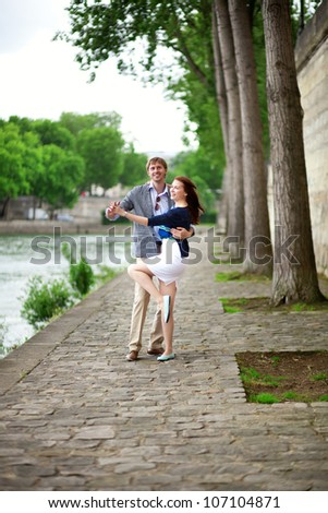 Positive laughing couple is dancing on the Seine embankment in Paris