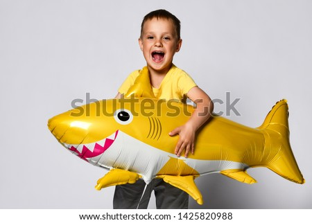 Positive little boy hold a balloon in the shape of a yellow shark fish, celebrate the holiday, smiling widely, stand on a light background, are in a good mood.