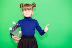 Positive little ecologist girl holding trash bag with plastic bottles and show thumb up isolated on green background. Ecology environment problem consumption. Reducing consumption of plastics is