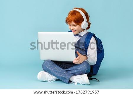 positive little red-haired schoolboy in headphones smiling and  learn remotely on modern laptop while sitting crossed legged on blue background Stock photo ©