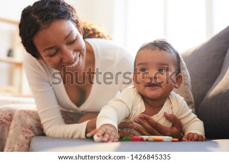 Positive loving young black mother spending beautiful time with her baby on maternity leave at home Stock photo ©