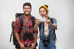 Positive male and female adventurers having happy expressions posing in camera of their modern smart phone isolated over white wall with copy space. Cheerful friends having hiking trip together