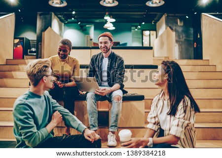 Positive male and female multiracial colleagues satisfied with cooperation share ideas and opinions,  cheerful creative guy with laptop computer talking with friend on meeting planning startup