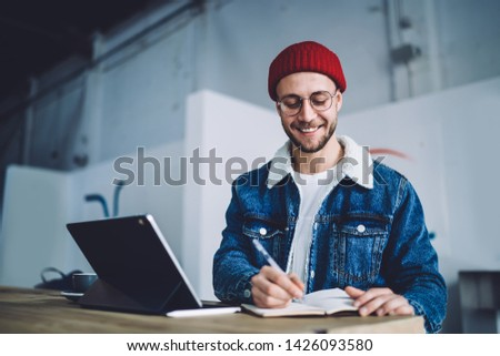 Positive male copywriter making memo notes for creating content publication while recording general concepts about blogging into paper textbook, Caucasian smiling hipster guy in classic glasses