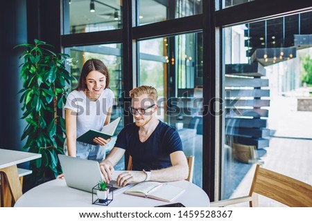 Positive male copywriter posting article on content website while female friend standing near with textbook in hand and giving consultancy about 4g connection on laptop computer,concept of cooperation