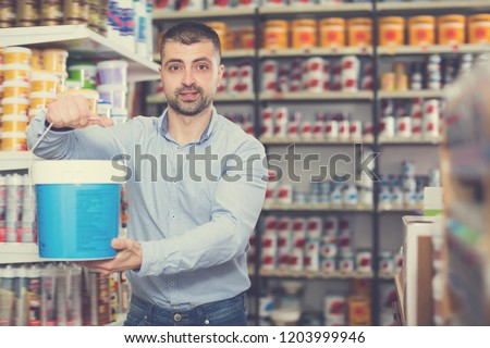 Positive male designer is holding paint for redecorate room in the store