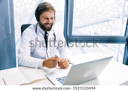 positive male doctor in white uniform wearing headset consults with a hospital patient online on a laptop, a smiling young GP man in headphones has a video call with a clinic client