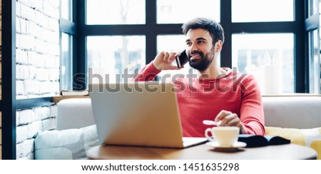 Positive male freelancer making cellphone call sitting with modern laptop computer in coworking cafeteria, handsome smiling hipster guy enjoying mobile phone conversation connected to 4g internet