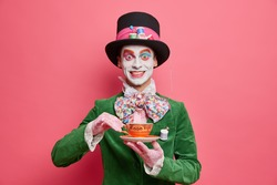 Positive male hatter enjoys tea party dressed in hat and green velvet jacket poses against rosy background looks like real gentleman. Fictional character from wonderland in carnival costume.