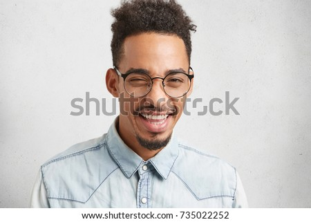 Positive male with beard and mustache blinks with eyes, smiles or grins, has good mood after noisy party with friends. Hipster guy has African hairstyle wears formal clothes, isolated over white wall - Shutterstock ID 735022252