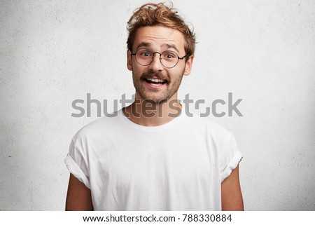 Positive male wonk has funny expression, being in high spirit, dressed casually, rejoices success and achievning great popularity in sphere he is involved, stands against white concrete background #788330884