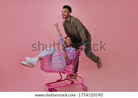 Positive man and woman having fun and riding shopping cart on pink background. Cheerful guy in brown sweater and pants posing with girlfriend on isolated