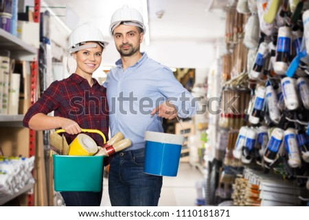 Positive man and  woman in helmets are holding paint and all instruments for redecorate room in the store