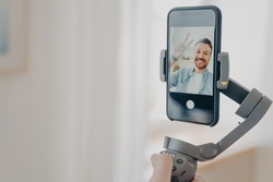 Positive man blogger holding gimbal stabilizer with smartphone and trying to make selfie pictures and live video while spending time at home in living room. Vlog and video blogging concept