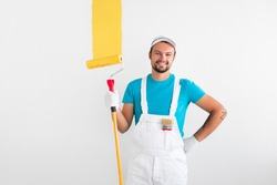 Positive man in uniform and with paint roller holding hand on waist and smiling for camera while coloring wall with yellow pigment during renovation works