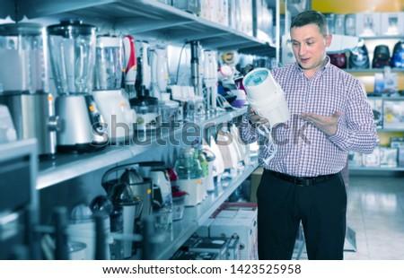 Positive man is choosing blender for his kitchen in appliances shop