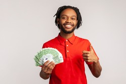 Positive man with dreadlocks wearing red casual T-shirt, holding bunch of euro banknotes and showing thumbs up gesture, sign of success, approval. Indoor studio shot isolated on gray background.