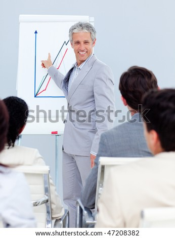 Positive mature businessman doing a presentation to her team