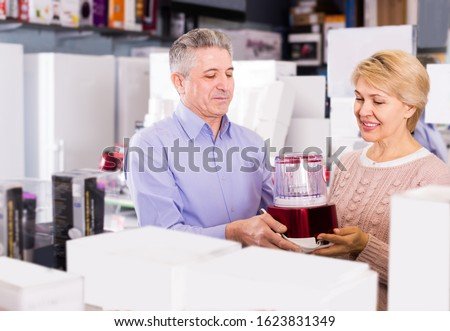 positive mature married couple in shopping center buys small kitchen household appliances for their home