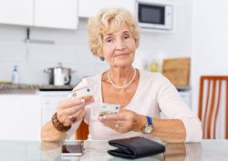 Positive mature woman counting her cash sitting at the kitchen table