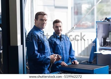 Positive mechanics standing in car service center #519962272