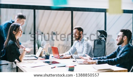 Positive men and woman communicate during working time on personal topics after planning trade occupation, successful colleagues sitting at desktop with computers and enjoying friendly conversation