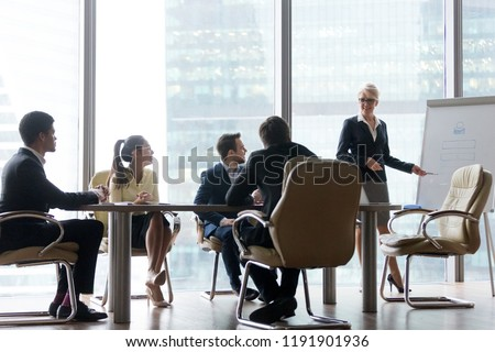 Positive middle-aged female coach or mentor training employees, making flipchart presentation at meeting, smiling mature businesswoman present project or idea to colleagues at office negotiations