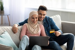 Positive middle-eastern couple buying plane tickets online, using laptop and credit card, sitting on couch in living room, copy space. Muslim family planning vacation, booking hotel on internet