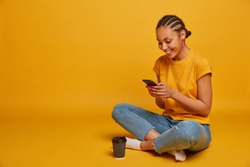 Positive millennial girl with dark skin, braided hairstyle, sits crossed legs and holds telephone, checks followers, sends messages, drinks takeaway coffee, isolated on yellow background, empty space