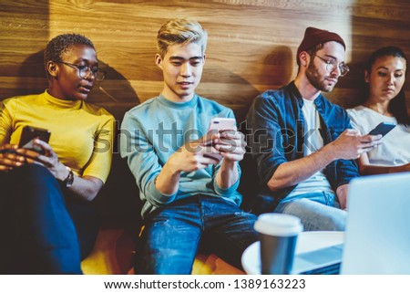 Positive millennial hipster guys using their smartphones ignore real conversation, trendy dressed hipsters addicted to modern technologies and internet networking and chatting via smartphones 