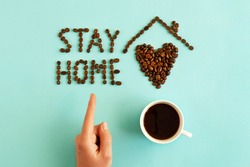 Positive mock up with objects: Stay home inscription made from coffee beans, symbolic heart and house, cup with hot drink and mans hand pointing to movers phrase. Stay at home and drink coffee concept
