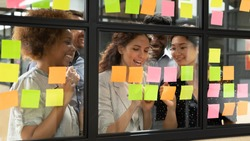 Positive multi-ethnic group of business people working together on new project writing main topics sharing creative ideas thoughts using colourful post-it sticky notes, concept of synergy and teamwork