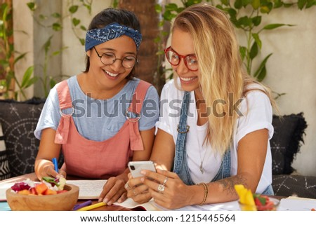 Positive multiethnic students with happy expression watch video from social networks, view photos, have break after studying, pose in cosy place, write records in notebook, eat exotic fruit salad