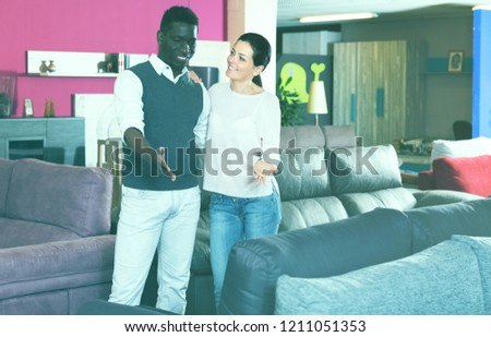 Positive multinational couple is choosing new furniture for interior their room in the store