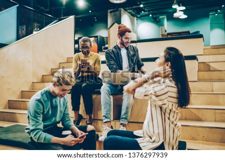 Positive multiracial colleagues communicating during free time on break in campus using modern gadgets, group of male of female hipsters spending time together share creative ideas and networking