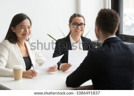 Positive multiracial hr team or friendly female executives laughing at funny joke during successful job interview with male winning applicant making good first impression, humor and hiring concept