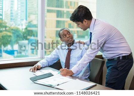 Positive new team member asking mentor about project. Standing Indian in formal wear explaining sitting Afro American paper graphs. Training concept