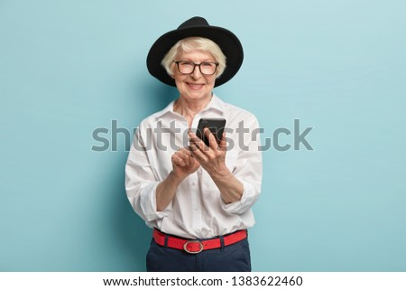 Positive old lady with wrinkled face, happy finally to learn how use smartphone and internet, wears transparent glasses, black hat, stylish shirt and trousers, isolated over blue background.