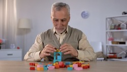 Positive old man playing with wooden cubes, cognitive training in Alzheimer
