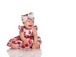 Positive overjoyed baby girl wearing beautiful festive dress and laughing sitting on white floor studio shot isolated on white background. Lovely female kid portrait. Happy infancy. Child fashion