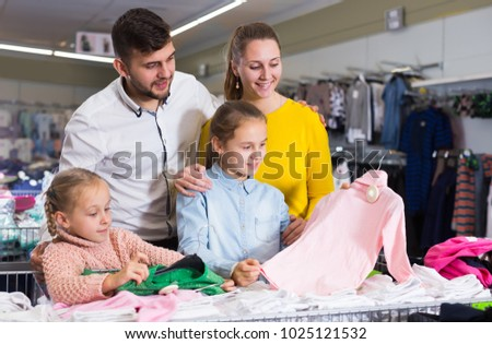 Positive parents choosing new turtleneck for daughters in children clothing shop
