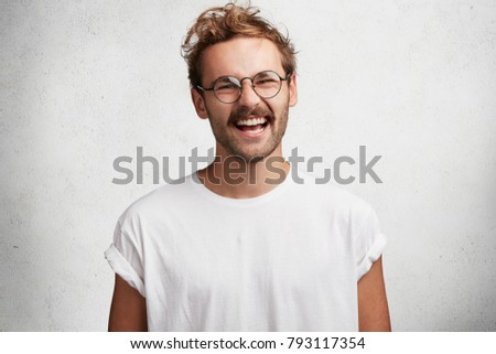 Positive pleased handsome stylih young man in round eyewear and casual t shirt, laughs at something funny, being in good mood as spends free time at circle of friends, expresses real happiness #793117354