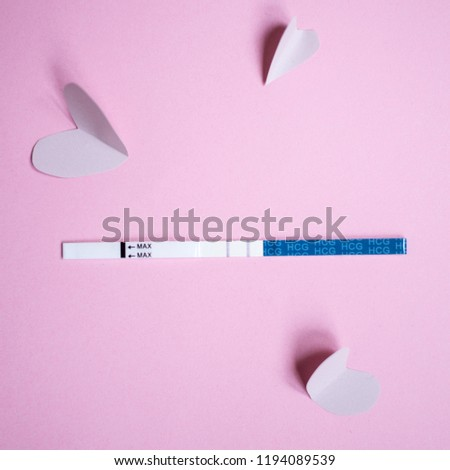 Positive pregnancy test with two strips and pink hearts. pink background, copy space #1194089539