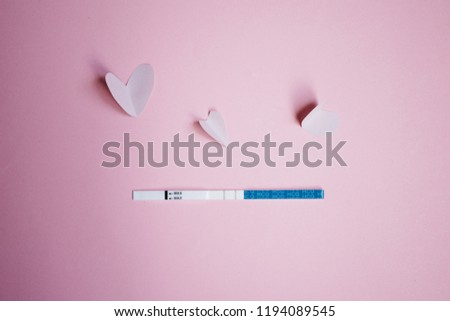 Positive pregnancy test with two strips and pink hearts. pink background, copy space #1194089545