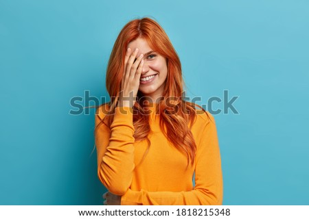 Positive redhead European woman makes face palm and feels shy hears hilarious joke and giggles positively dressed in casual orange jumper isolated on blue background. Happy emotions or feelings ストックフォト ©