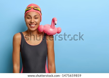 Positive restful dark skinned woman ready for swimming, carries inflated circle on shoulder, wears bathing suit stands against blue studio wall has fun and laughs during vacation enjoys summer by pool