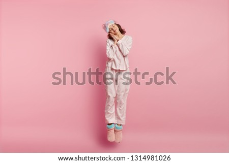 Positive restful lovely woman with eyes shut, enjoys sleeping at home, leans on hands, jumps in air, wears eyemask, nightclothes, isolated over pink background. Bed time concept #1314981026