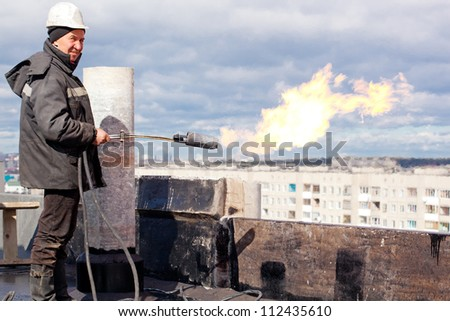 Positive roofer workman in uniform with a gas torch during roofing works