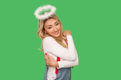 Positive self-esteem. Portrait of angelic adult woman embracing herself and smiling, satisfied with her appearance, no insecurities, self-love concept. indoor studio shot isolated on green background