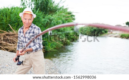 Positive senior man angling on river and trying to catch fish